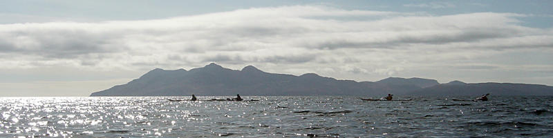 Paddling back down the Sleat coast in improving conditions, with Rum behind. Photo: Andy Waddington.