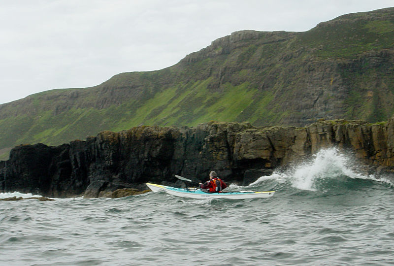 Ann Jones paddling close to the rocks of Ulva in the swell. Photo: Andy Waddington.